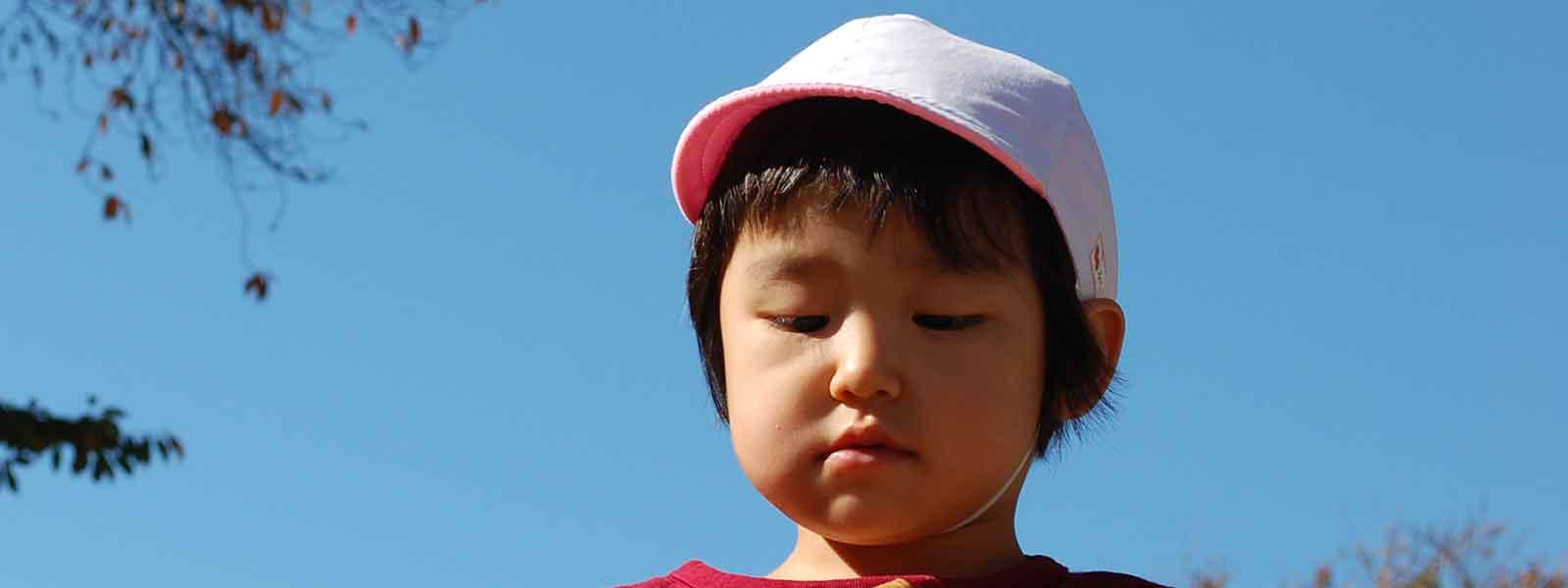 青空をバックにした子どもの表情